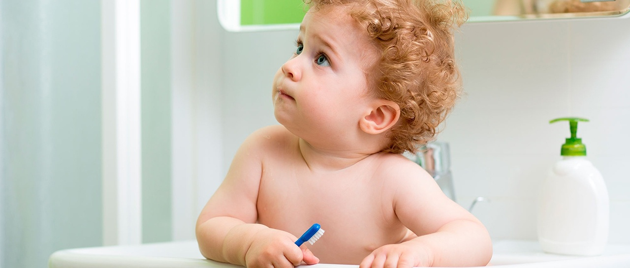 Baby i vask på badet med tannbørste i hånda