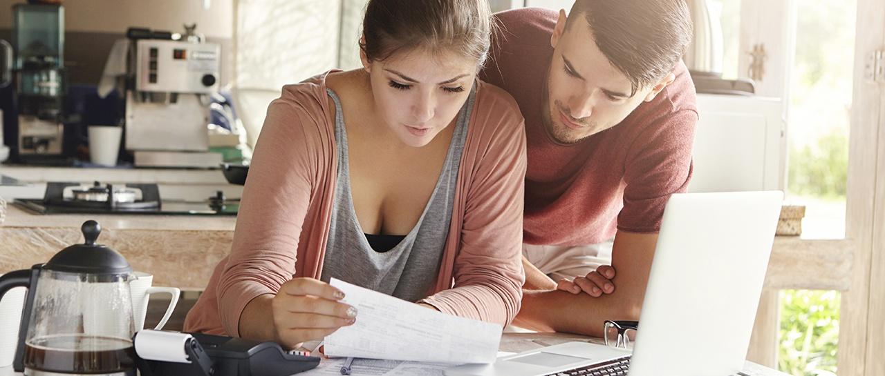 Kvinne og mann leser faktura på kjøkkenet